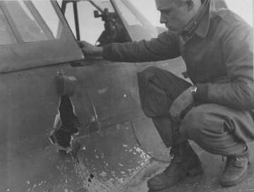 87th-FS-Gordon-AcMoody-inspects-damage-to-his-P-40-X78-Capodichino-Naples-Italy-January-1944.-Still-from-USAAF-film-1