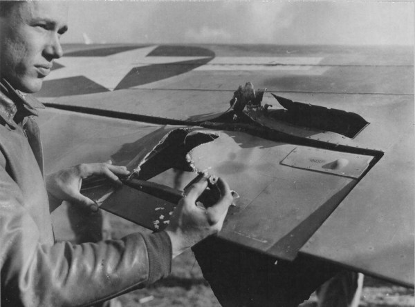 87th-FS-Gordon-AcMoody-inspects-damage-to-his-P-40-X78-at-Capodichino-Naples-Italy-in-January-1944.-Still-from-USAAF-film-3