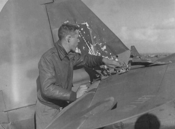 87th-FS-Gordon-AcMoody-inspects-damage-to-his-P-40-X78-at-Capodichino-Naples-Italy-in-January-1944.-Still-from-USAAF-film-4